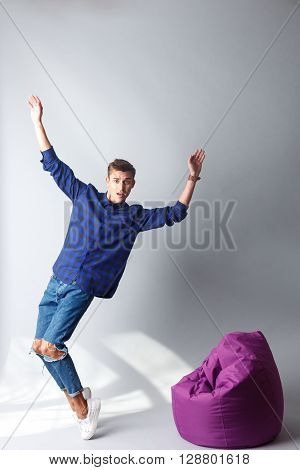 Full length portrait of handsome young man standing and falling on flexible chair. He is raising arms up and looking at camera with disappointment. Isolated