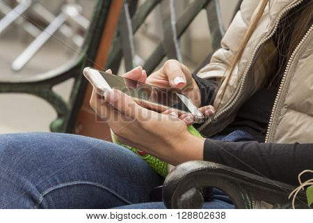 the girl in the arm with a French manicure keeps mobile phone