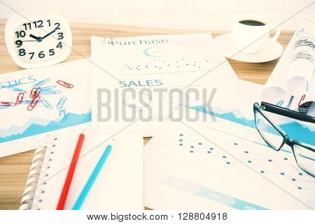 Wooden tabletop with business reports glasses clock and other items