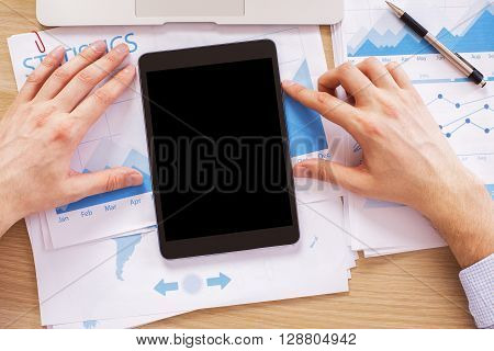 Male hands with black tablet on wooden desk with business report. Topview Mock up