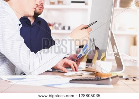 Sideview of businessmen discussing business diagrams and pointing at computer screen in office