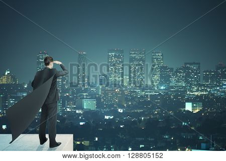 Businessman with black superhero cape standing on pedestal and looking into the distance on night city background