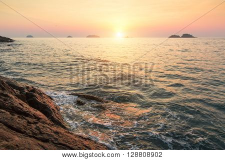 Sunset on a tropical rocky shore.