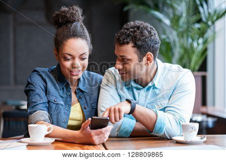 Pretty young loving couple is using a mobile phone in cafe. They are sitting at desk. The man is looking at girl with joy. The woman is smiling happily