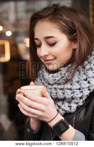 Cheerful girl is holding a cup of latte and warming her hands. She is standing outside on in winter clothing. The lady is smiling