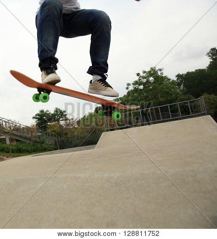 closeup of skateboarding woman practice ollie at skatepark