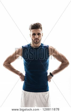 Portrait of cheerful fit sportsman standing with arms akimbo. He is looking at camera with aspiration. Isolated