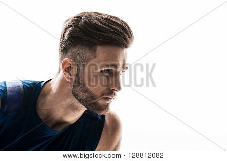 Portrait of attractive young athlete ready to run. He is standing in pose and looking forward with confidence. Isolated and copy space in right side