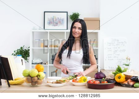 Young beautiful housewife in the kitchen, cutting fresh green vegetable, smiling, looking at camera.  Opened cookbook with recipes on cook work table