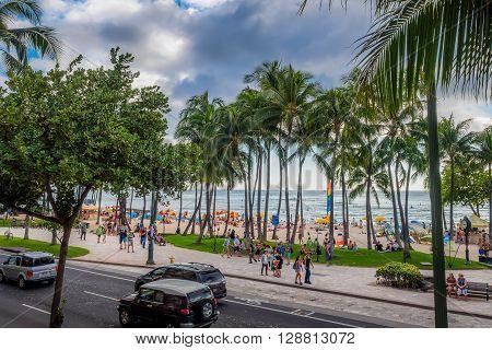 Honolulu, Hawaii, USA - Dec 15, 2015: Waikiki Beach and visitors, near the Kuhio Beach Hula Mound. Cars drive along Kalakaua Avenue. This image features a dramatic sky, signalling an approaching rain.