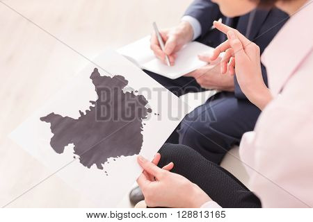 Close up of female hands holding a picture. She is sitting and telling the psychologist what she sees on it. The doctor is writing her ideas down