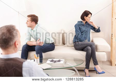 Young family has problems in their marriage. Man and woman are sitting on sofa separately with insult. The psychologist is giving them advice