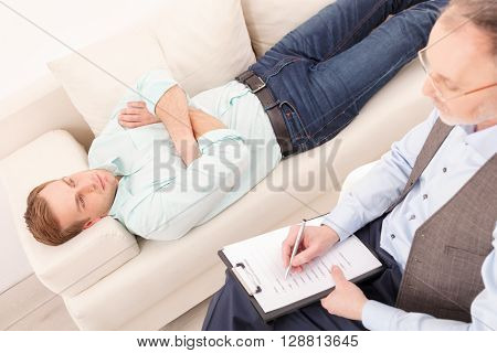 Professional mature psychologist is consulting young man. He is sitting and making notes with seriousness. The guy is lying while experiencing stress