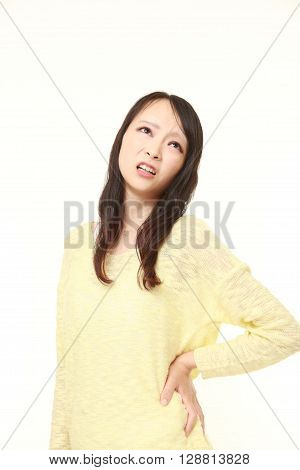 portrait of Japanese woman suffers from lumbago on white background