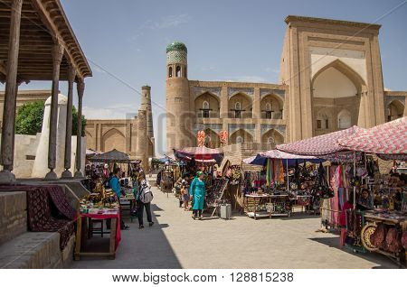KHIVA, UZBEKISTAN - April 30, 2015: The square with the complex of two old Madrasah - Kutlimurodinok and Allakuli Khan and the Oq mosque converted into the rug store