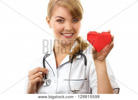 Smiling woman doctor cardiologist in white apron with stethoscope holding red heart of paper healthcare and medicine concept white background