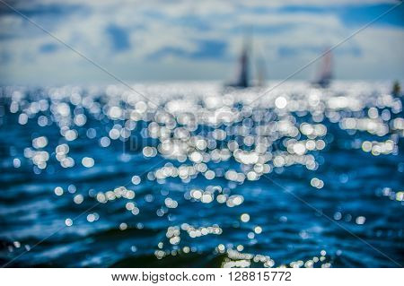 Beautiful abstract background bokeh sun light reflections on blue aqua water sailing boat