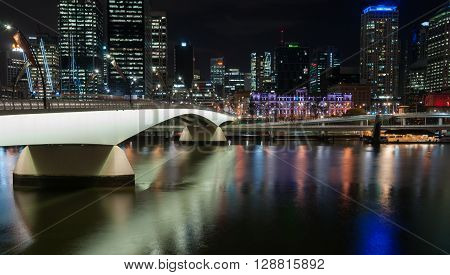 Brisbane, Australia - April 27, 2016; Brisbane Victoria Bridge iluminated against dark and city building lights and colr reflections in calm water of Brisbane River