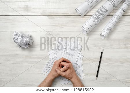 Closeup masculine folded hands on wooden panel with hand-folding a piece of paper. Worry process. Top view composition. Anger sign. Workplace of architect or constructor. Engineering work. Construction and architecture. Architect drawing. Draft.