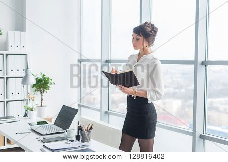 Portrait of a young female assistant planning work day schedule, writing down timetable, standing in office