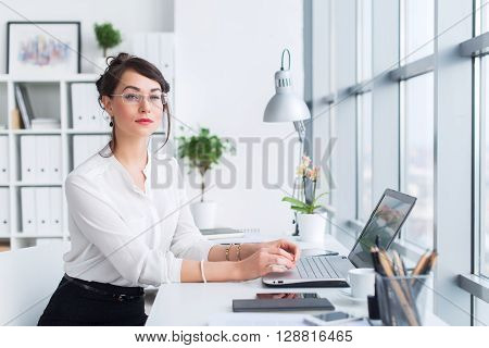 Young businesswoman sitting at her workplace, working out new business ideas, wearing formal suit and glasses, looking aside