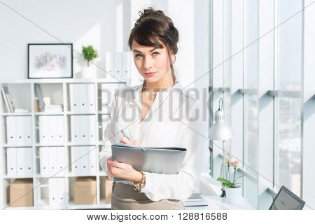 Close-up portrait of a caucasian female office assistant at her workplace. Confident clerk, standing, holding document folder