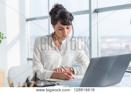 Female writer working in light modern office, writing down new ideas in her notebook, searching information using portable computer at workplace
