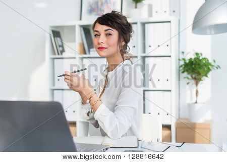 Young attractive office worker drinking cup of tea, having coffee break in the morning, getting ready for work day
