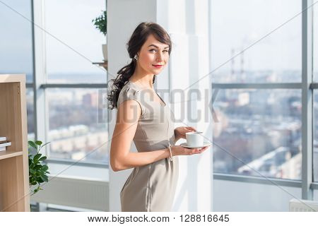 Elegant young woman standing in a spacious light studio, drinking cup of coffee, smiling, dreaming near large window, having break during work day