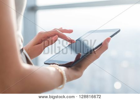 Close-up photo of female hands working with tablet computer. Woman using social network, texting and blogging