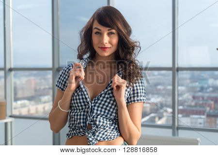 Front view portrait of a glamorous young woman standing in appealing pose, flirting, holding shirt collar with her hands