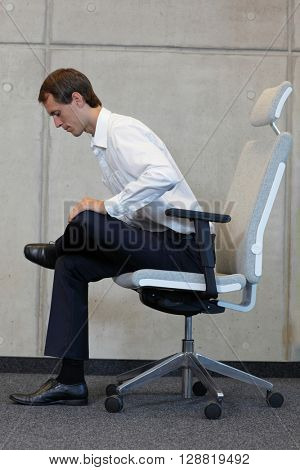 yoga with chair in office - business man exercising