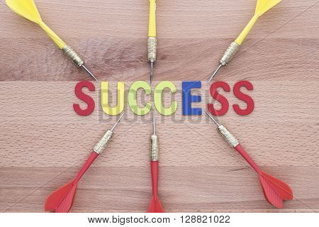 Six dart run in to success target on wooden background. Group of dart (Teamwork) run in to Success target. Abstract success background concept