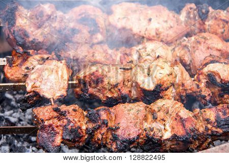 barbecue a shish kebab pork on skewers over charcoal.