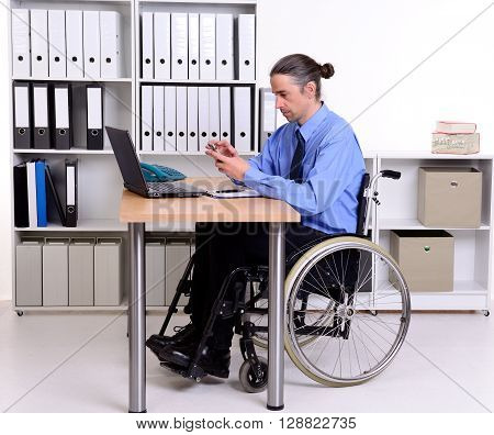 disabled business man in wheelchair using his smartphone