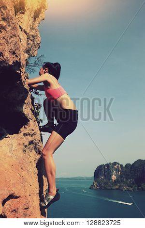 young woman rock climber climbing at seaside