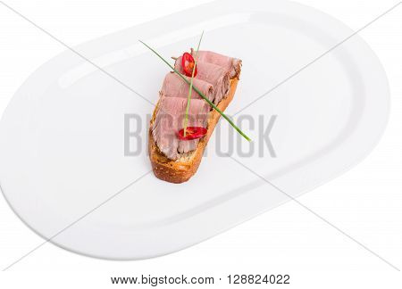 Delicious italian bruschetta with roast beef and fresh scallions. Isolated on a white background.