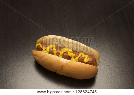 Hot dog with mustard on a bun