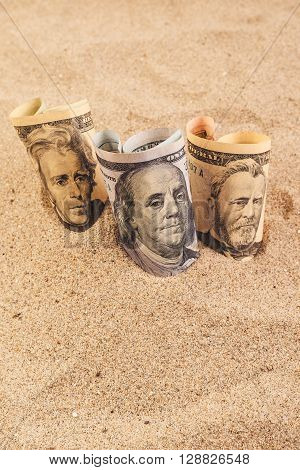 American dollar banknotes in hot desert sand