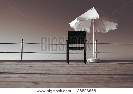 Lonely armchair on a wooden pier near the sea