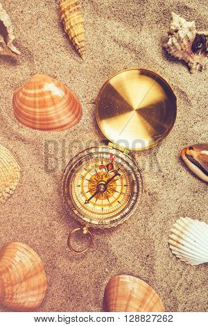 Top view of vintage compass and sea shells on sandy beach navigational equipment in warm brown sand of summer holiday vacation resort pointing to south.