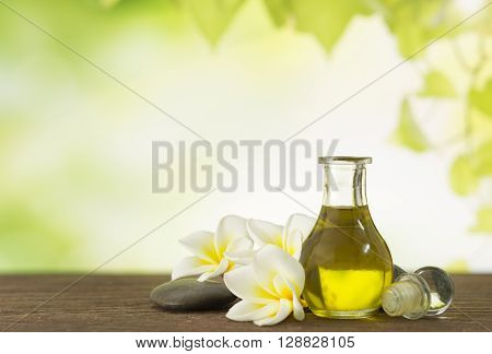 Aroma oil massage with frangipani flower and natural background. Spa concept.