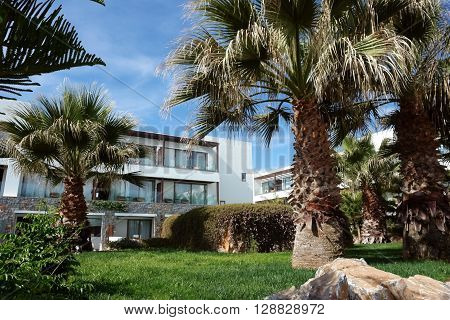 HERAKLION, CRETE, GREECE - MAY 13, 2014: The blue sky modern building with balcones and palms on the terrain of luxury class hotel Grecotel Amirandes on the Mediterranean coast of Crete, May 13, 2014, Greece.