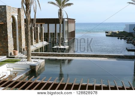 HERAKLION, CRETE, GREECE - MAY 13, 2014: The big blue swimming-pool modern building with columns palms and beach in luxury class hotel Grecotel Amirandes on the Mediterranean coast of Crete, May 13, 2014, Greece.