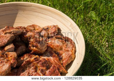 hot grilled pork in a bowl on a green grass