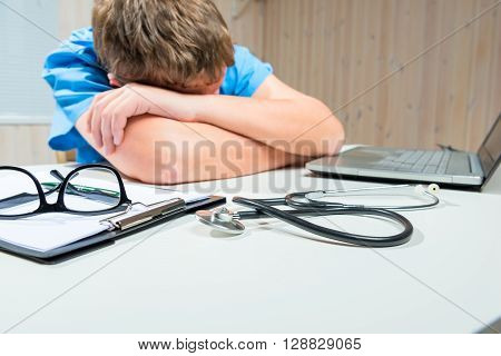 Tired Doctor Sleeps At The Table In Working Hours In The Office