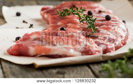 fresh raw pork ribs with herbs on vintage background
