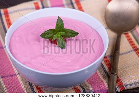 Strawberry and raspberry smoothie with cream cheese on a white plate close up