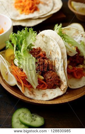 Mexican Tacos With Ground Beef And Different Vegetables On A Wooden Plate