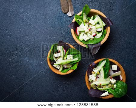 Three healthy vegetable salads with pumpkin seeds in wooden bowls on a dark background